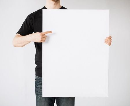 Photo for close up of man hands showing white blank board - Royalty Free Image