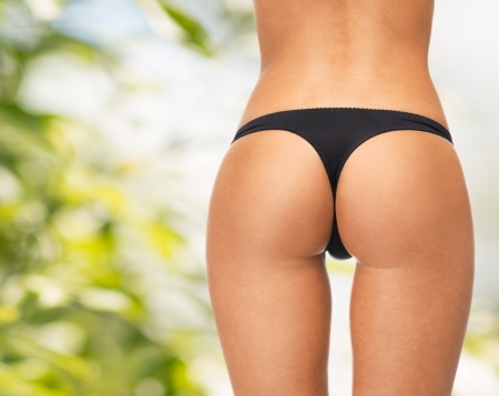 Photo for picture of female legs in black bikini panties - Royalty Free Image