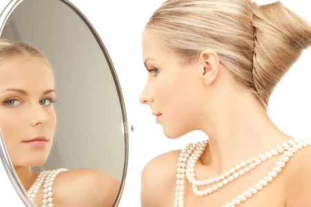Photo pour woman with necklace from pearls and looking into the mirror - image libre de droit
