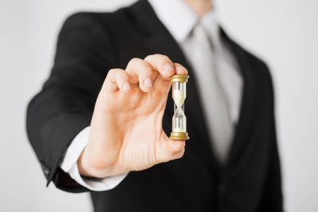 Foto de close up of man hand holding hourglass  - Imagen libre de derechos