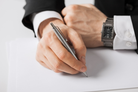 Photo for picture of businessman writing something on the paper - Royalty Free Image