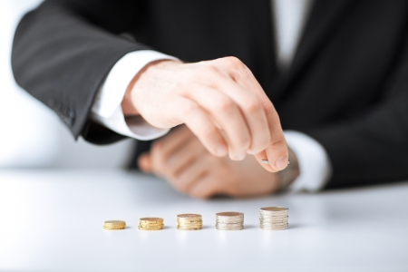 Photo pour picture of man putting stack of coins into one row - image libre de droit