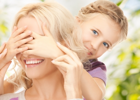Photo for picture of mother and daughter making a joke or playing hide and seek - Royalty Free Image