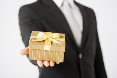Photo pour close up of man hands holding gift box. - image libre de droit