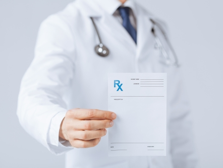 Photo pour close up of male doctor holding rx paper in hand - image libre de droit