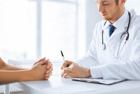 Photo pour close up of patient and doctor taking notes - image libre de droit