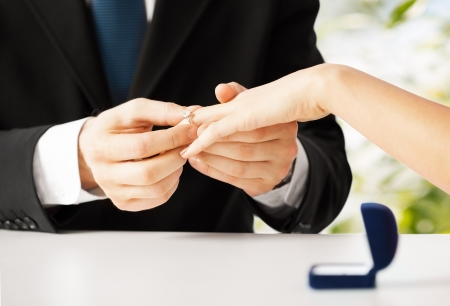 Foto per picture of man putting  wedding ring on woman hand - Immagine Royalty Free