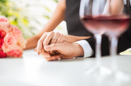 Photo pour picture of engaged couple with wine glasses in restaurant - image libre de droit