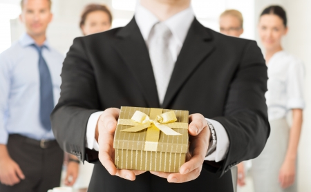 Foto de close up of man hands holding gift box in office - Imagen libre de derechos