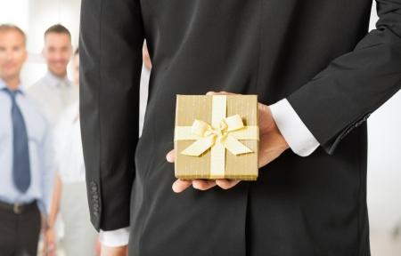 Photo pour close up of man hands holding gift box in office - image libre de droit