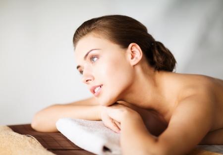 Foto de beauty and spa concept - woman in spa salon lying on the massage desk - Imagen libre de derechos