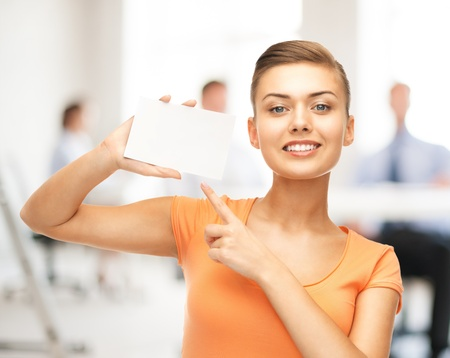 Photo pour smiling woman pointing at white blank card in office - image libre de droit