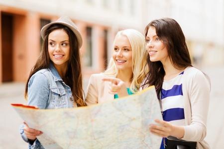 Foto de holidays and tourism concept - beautiful girls looking for direction in the city - Imagen libre de derechos