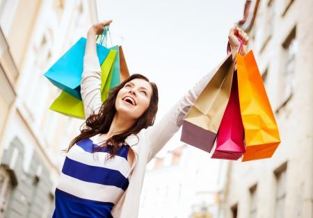Foto de shopping and tourism concept - beautiful woman with shopping bags in ctiy - Imagen libre de derechos