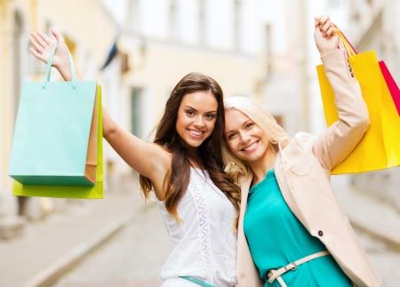 Foto de shopping and tourism concept - beautiful girls with shopping bags in ctiy - Imagen libre de derechos