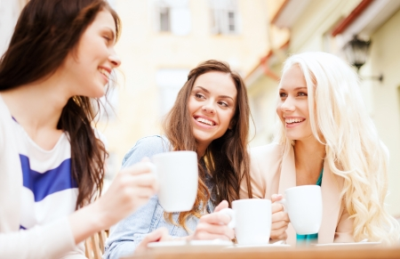 Photo pour holidays and tourism concept - beautiful girls drinking coffee in cafe - image libre de droit