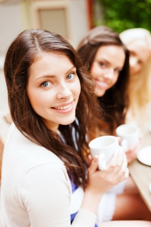 Foto de holidays and tourism concept - beautiful girls drinking coffee in cafe - Imagen libre de derechos
