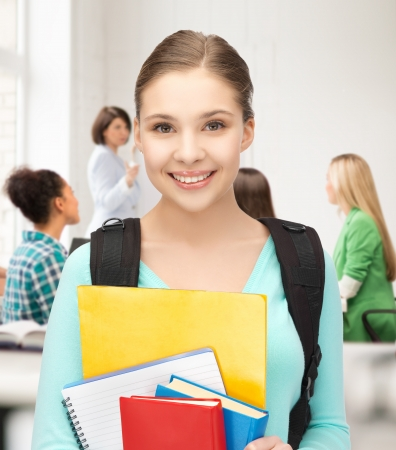 Foto de happy student girl with school bag and notebooks at school - Imagen libre de derechos