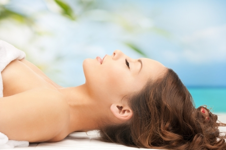 Photo pour beauty and spa concept - woman in spa lying on the massage desk - image libre de droit