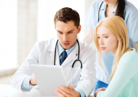 Foto de healthcare, medical and technology - doctor showing something patient on tablet pc in hospital - Imagen libre de derechos