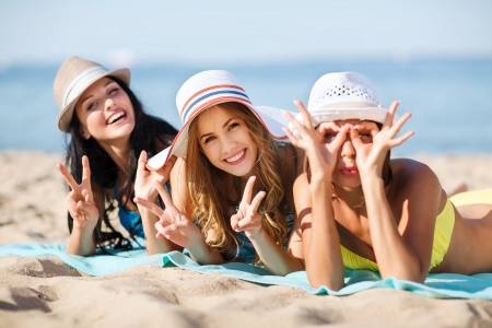 Photo pour summer holidays and vacation - girls sunbathing on the beach - image libre de droit
