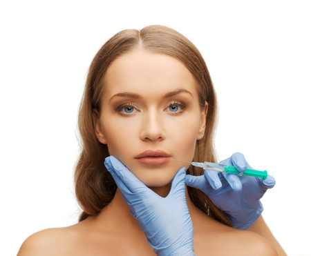 Photo for cosmetic surgery concept - woman face and beautician hands with syringe - Royalty Free Image