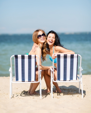 Photo for summer holidays and vacation - girls in bikinis sunbathing on the beach chairs - Royalty Free Image
