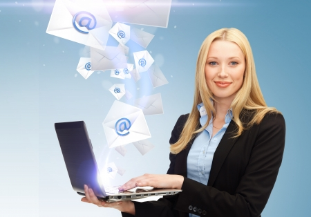Foto de business, communication and internet concept - businesswoman holding laptop with email sign - Imagen libre de derechos