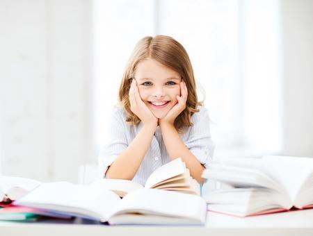 Foto de education and school concept - little student girl studying and reading book at school - Imagen libre de derechos