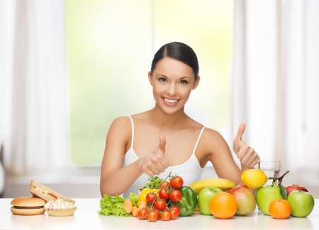 Foto per healthy and junk food concept - woman with fruits rejecting hamburger and cake - Immagine Royalty Free