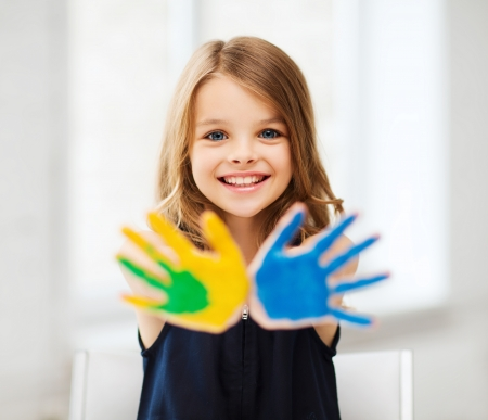 Foto de education, school, art and painitng concept - little student girl showing painted hands at school - Imagen libre de derechos