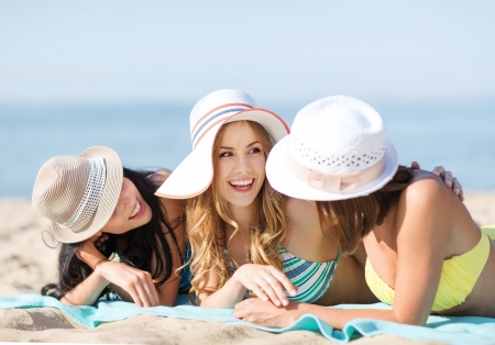 Photo for summer holidays and vacation - girls in bikinis sunbathing on the beach - Royalty Free Image