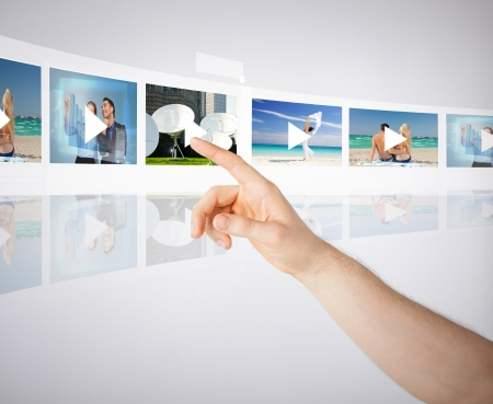 Foto de technology, internet, tv and virtual screens concept - man pressing button on virtual screen with videos - Imagen libre de derechos