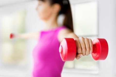 Photo for sport and recreation concept - sporty woman hands with light red dumbbells - Royalty Free Image