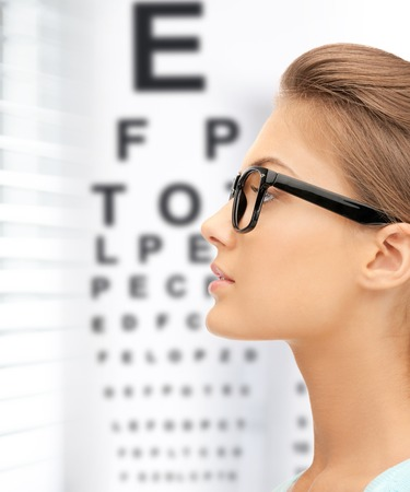 Foto de medicine and vision concept - woman in eyeglasses with eye chart - Imagen libre de derechos
