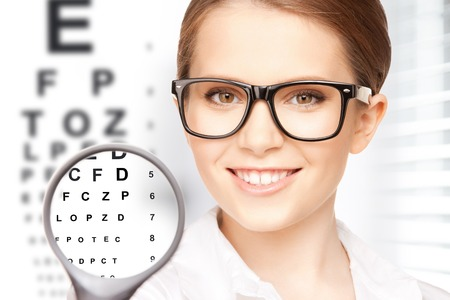 Foto de medicine and vision concept - woman with magnifier and eye chart - Imagen libre de derechos