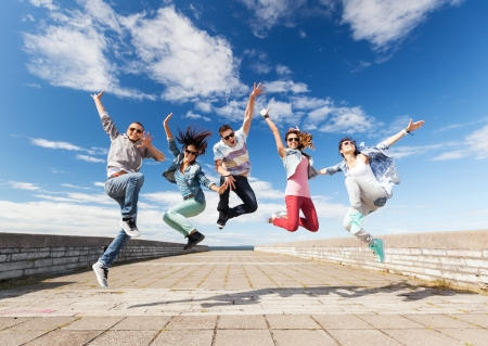 Foto de summer, sport, dancing and teenage lifestyle concept - group of teenagers jumping - Imagen libre de derechos