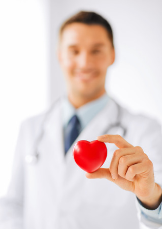 Foto de healthcare and medical concept - male doctor with heart - Imagen libre de derechos
