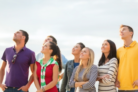 Photo for summer, holidays, vacation, happy people concept - group of friends looking up on the beach - Royalty Free Image