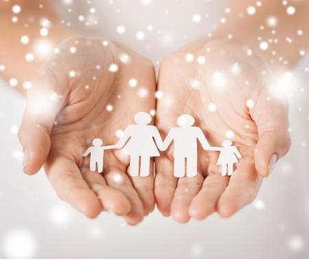 Foto de family, children, christmas, x-mas and happy people concept - woman cupped hands showing paper man family - Imagen libre de derechos