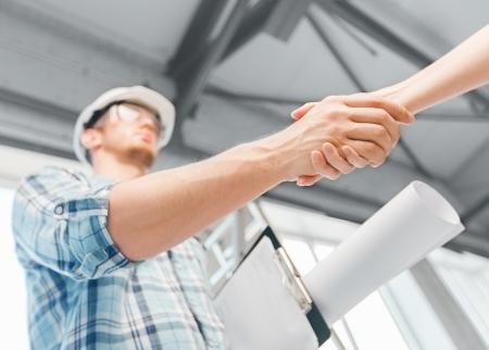 Photo pour architecture and home renovation concept - builder with blueprint shaking partner hand - image libre de droit