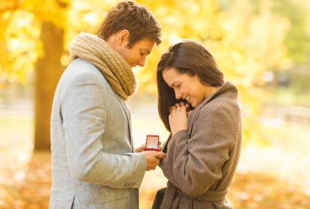 Photo pour holidays, love, couple, relationship and dating concept - romantic man proposing to a woman in the autumn park - image libre de droit