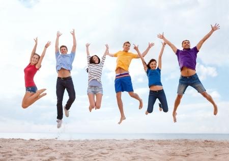 Foto de summer, holidays, vacation, happy people concept - group of friends jumping on the beach - Imagen libre de derechos