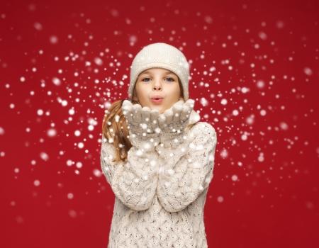 Foto de christmas, x-mas, people, happiness concept - happy girl in winter clothes blowing on palms - Imagen libre de derechos