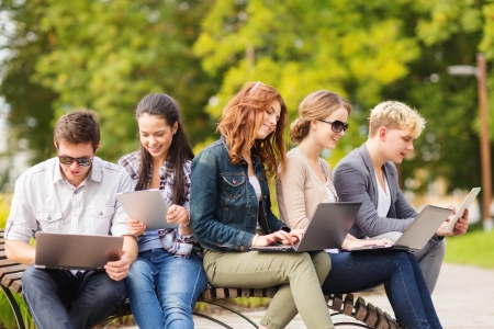 Foto de summer, internet, education, campus and teenage concept - group of students or teenagers with laptop and tablet computers hanging out - Imagen libre de derechos