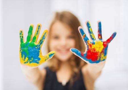 Foto de education, school, art and painitng concept - little student girl showing painted hands - Imagen libre de derechos
