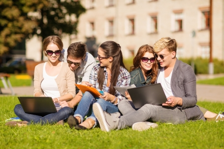summer, internet, education, campus and teenage concept - group of students or teenagers with laptop, notebooks, files and folders