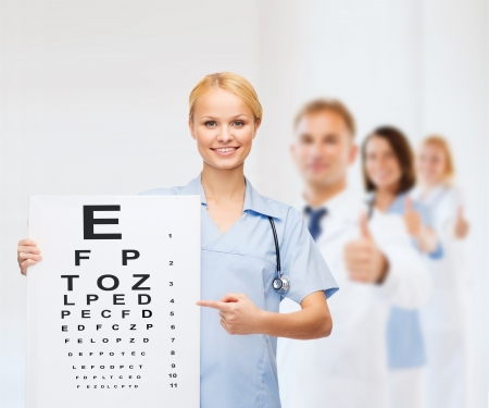Foto de healthcare, medicine, advertisement and sale concept - smiling female doctor or nurse with stethoscope and eye chart - Imagen libre de derechos