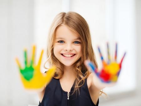 Foto de education, school, art and painitng concept - smiling little student girl showing painted hands at school - Imagen libre de derechos
