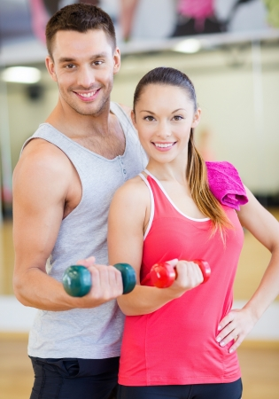 Foto de fitness, sport, training, gym and lifestyle concept - two smiling people working out with dumbbells in the gym - Imagen libre de derechos
